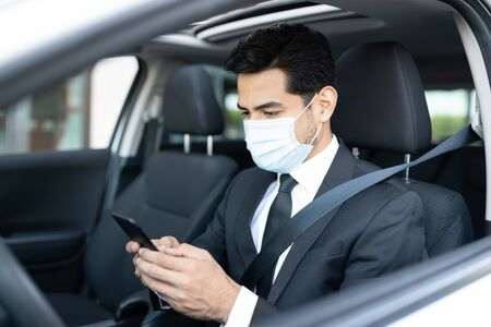 Young male driver using app on smartphone while sitting in car during coronavirus outbreak Stock Photo