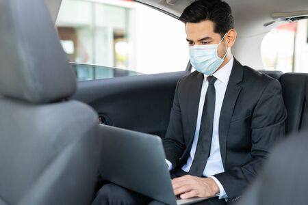 Businessman wearing face mask while using laptop in taxi during coronavirus outbreak