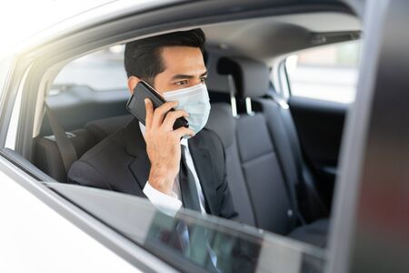 Businessman talking on mobile phone while wearing face mask in taxi during coronavirus crisis Imagens