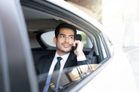 Confident Hispanic businessman talking on mobile phone while traveling in taxi Imagens