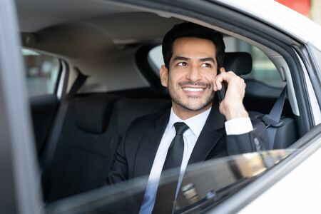 Smiling Latin young businessman talking on mobile phone while traveling in taxi