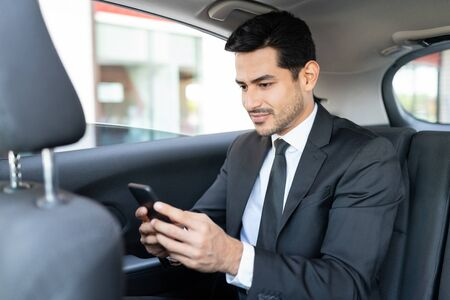 Hispanic young businessman text messaging through smartphone while traveling in taxi Imagens