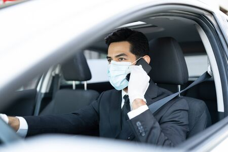 Male driver talking on mobile phone while wearing mask and gloves during coronavirus outbreak