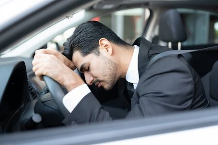 Tired young businessman sleeping on steering wheel in car