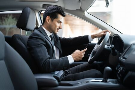 Confident businessman using smartphone while driving car in city 版權商用圖片