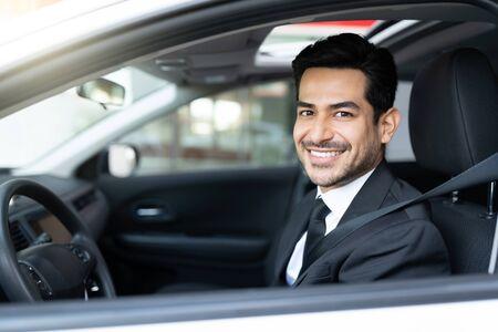 Smiling young Hispanic businessman driving car