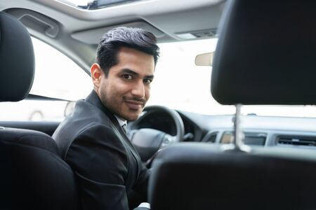 Confident young Hispanic businessman traveling in car