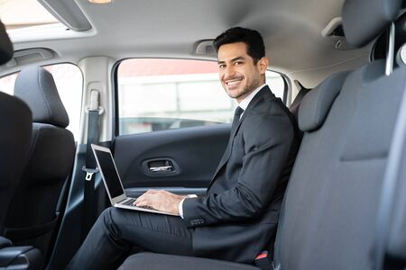 Portrait of smiling Hispanic young businessman using laptop while traveling in taxi