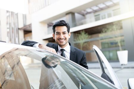 Portrait of confident young Latin businessman with new car