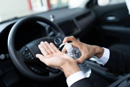 Cropped image of male driver pouring sanitizer on hand in car