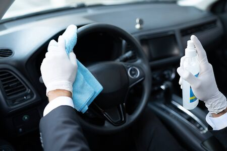 Cropped image of driver spraying sanitizer on steering wheel of car