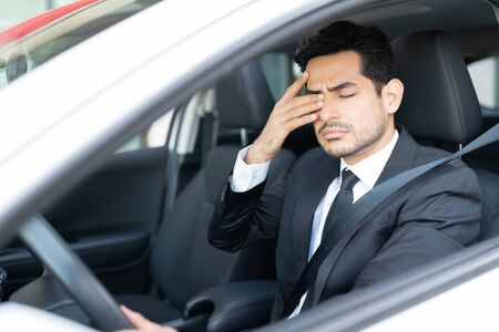 Tired young businessman rubbing eyes while driving car 版權商用圖片