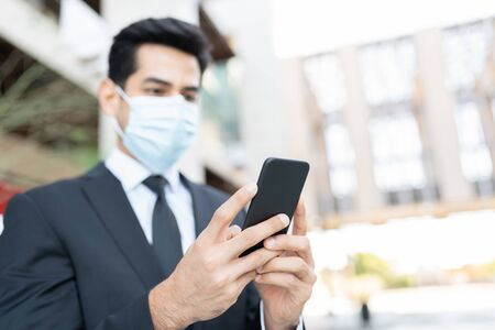 Young Hispanic male driver with face mask using app on mobile phone