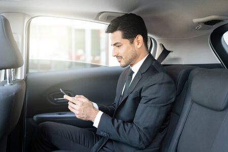 Side view of Latin young businessman text messaging through smartphone while traveling in taxi