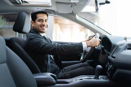 Smiling young Hispanic businessman driving car in city 版權商用圖片