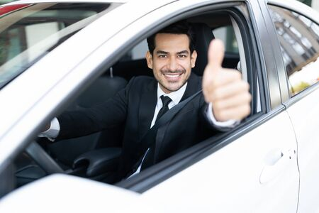 Portrait of confident young Latin businessman showing thumb up while driving new car