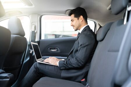 Side view of confident Latin young businessman using laptop while traveling in taxi Imagens
