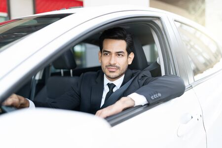 Thoughtful young Latin businessman looking away while driving car in city