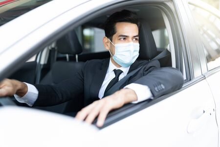 Young businessman wearing face mask while driving car in city during coronavirus outbreak