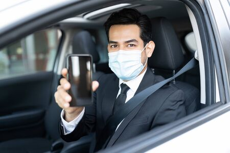 Portrait of young male driver showing smartphone while sitting in car during coronavirus crisis 版權商用圖片
