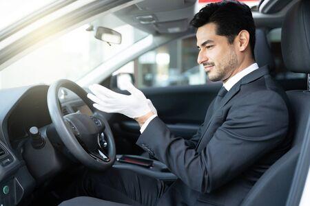 Confident Hispanic male driver wearing gloves in car during coronavirus outbreak 版權商用圖片