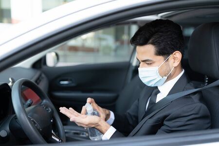 Young male driver pouring sanitizer on hand while sitting in car