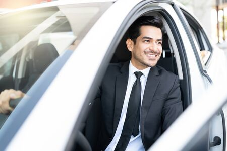 Confident good looking young Hispanic businessman in car