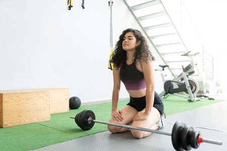Latin young woman resting after barbell workout at health club Banque d'images
