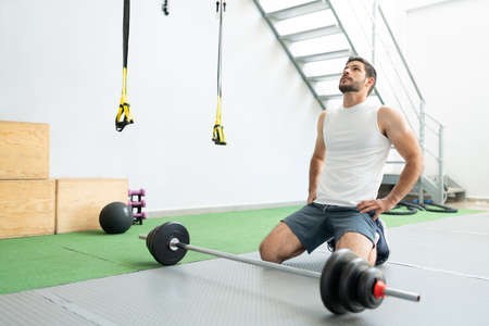 Hispanic young man taking break after doing workout with barbell at health club Banque d'images