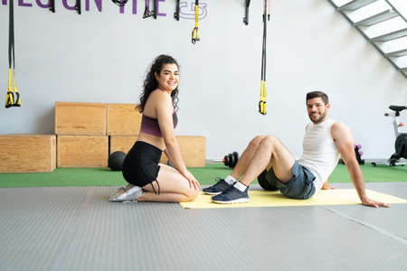 Confident fit young woman and man exercising together at health club Banque d'images