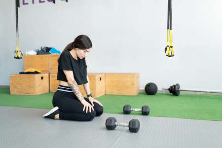 Hispanic sporty young woman taking break during workout at health club