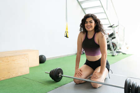 Smiling Hispanic young woman kneeling and resting in fitness club