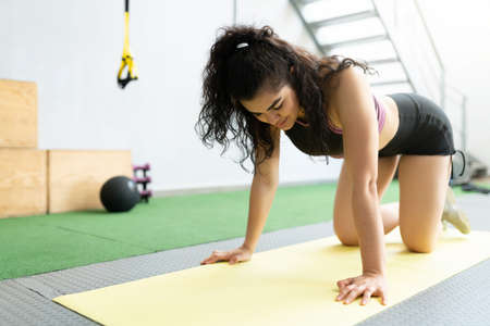 Active young woman looking tired after exercising on a mat at fitness studio