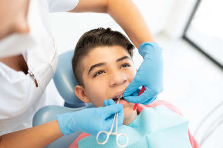 Female orthodontist changing rubber bands on braces of teenage boy
