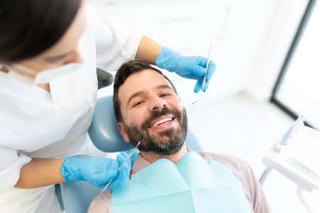 Female dentist checking man with carver and mirror at dental clinic