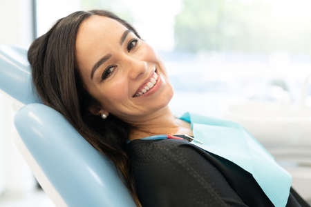 Closeup of smiling attractive mid adult woman lying on chair at dental clinic