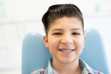 Closeup portrait of smiling cute Latin boy wearing braces in a dental clinic