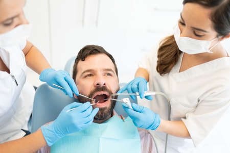 Pair of Female dentists examining mid adult man with tools at dental clinic