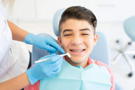 Dentists examining smiling teenage boy with dental mirror at clinic