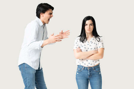 Young woman standing with arms crossed while man yelling on her in studio