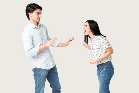 Angry young woman yelling at boyfriend against white background Imagens