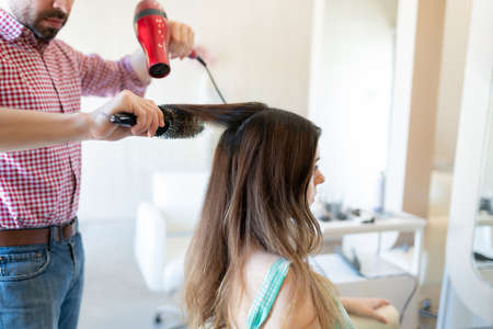 Male hairdresser using hair dryer on female client at salon 写真素材
