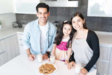 Portrait of happy family with milk and freshly made cookies at kitchen island
