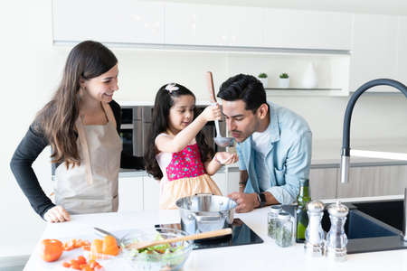 Father tasting food prepared by cute daughter in kitchen
