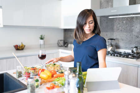 Young woman watching online recipe on digital tablet and preparing food in kitchen