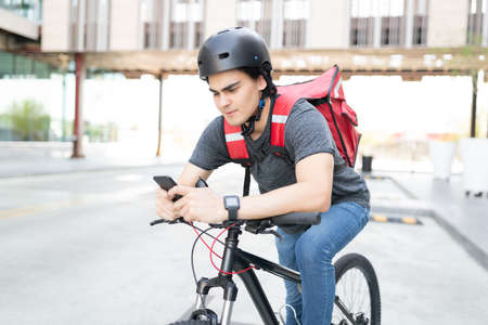 Handsome young delivery man using map on smartphone while riding bicycle