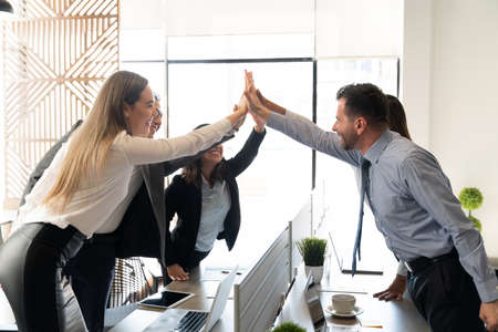 Business people standing around coworking desk in office and giving high five to each other