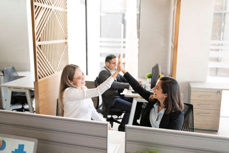 Two successful female colleagues giving high-five to each other while sitting at desk in workplace