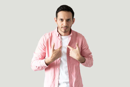 Attractive Latin man pointing at himself and looking puzzled in a studio with gray background Foto de archivo