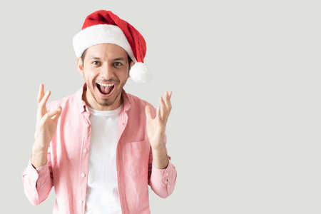 Hispanic man feeling great about Christmas and screaming excited in a studio with grey background